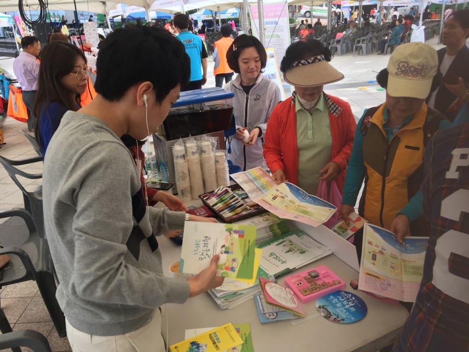 중구장애인복지관 홍보부스에서 홍보물을 보고 있는 사람들의 모습